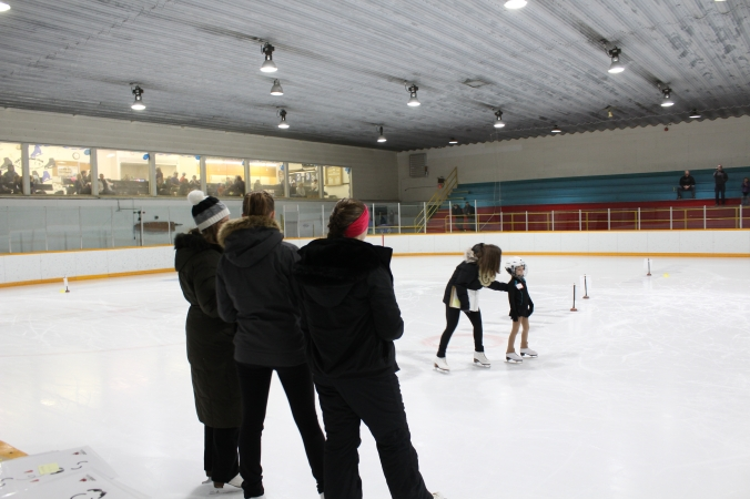 Coach, Erin Bay, helps a CanSkater under the watchful eye of the judges. (Photo credit:Tammy Karatchuk)